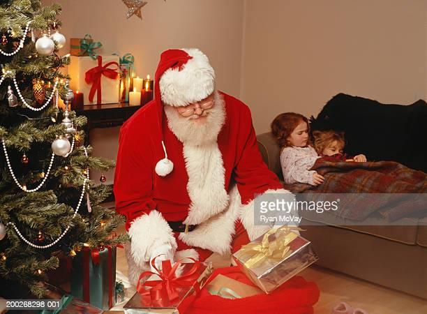 Santa Claus putting presents under Christmas tree