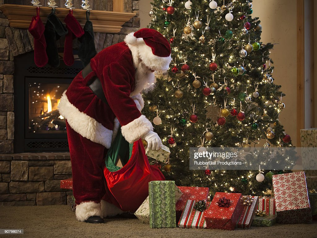 santa claus putting presents under the tree stock photo - Santa Claus Presents