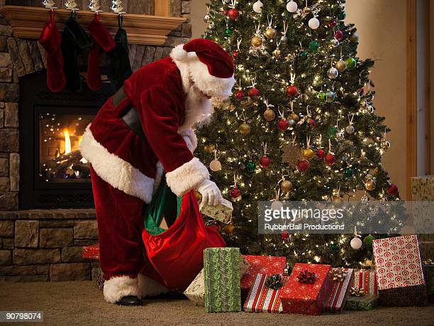 santa claus putting presents under the tree - santa stock pictures, royalty-free photos & images