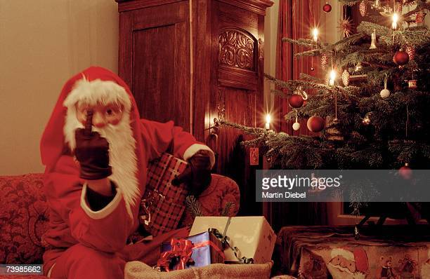 Santa Claus raising his middle finger whilst sitting on a sofa next to an illuminated Christmas tree
