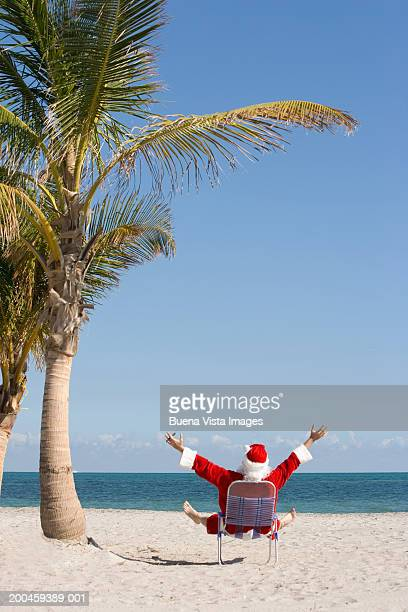 santa claus relaxing at beach, arms upraised, rear view - キービスケイン ストックフォトと画像