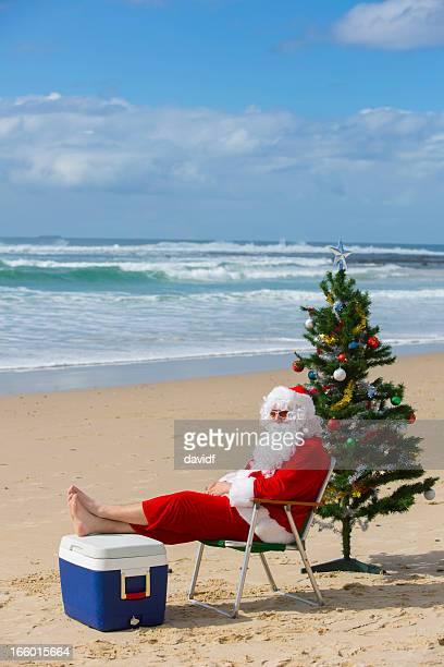 サンタクロースリラックスできるビーチで、クリスマスツリー