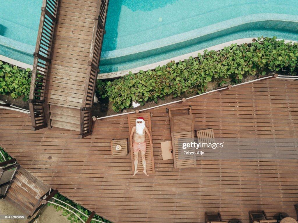 Santa Claus relaxing at the pool : Stock Photo