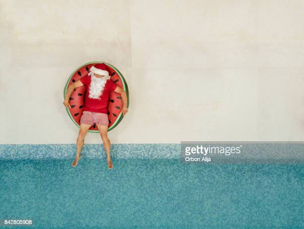santa claus relaxing at the pool - practical joke stock photos and pictures