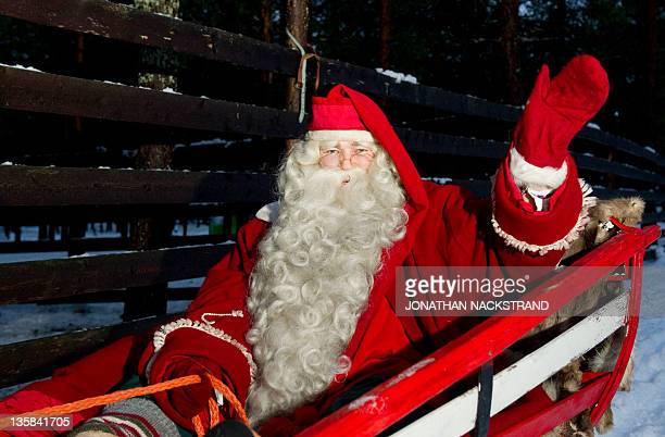 Santa Claus rides a reindeer and sled outside Rovaniemi Finnish Lapland on December 15 2011