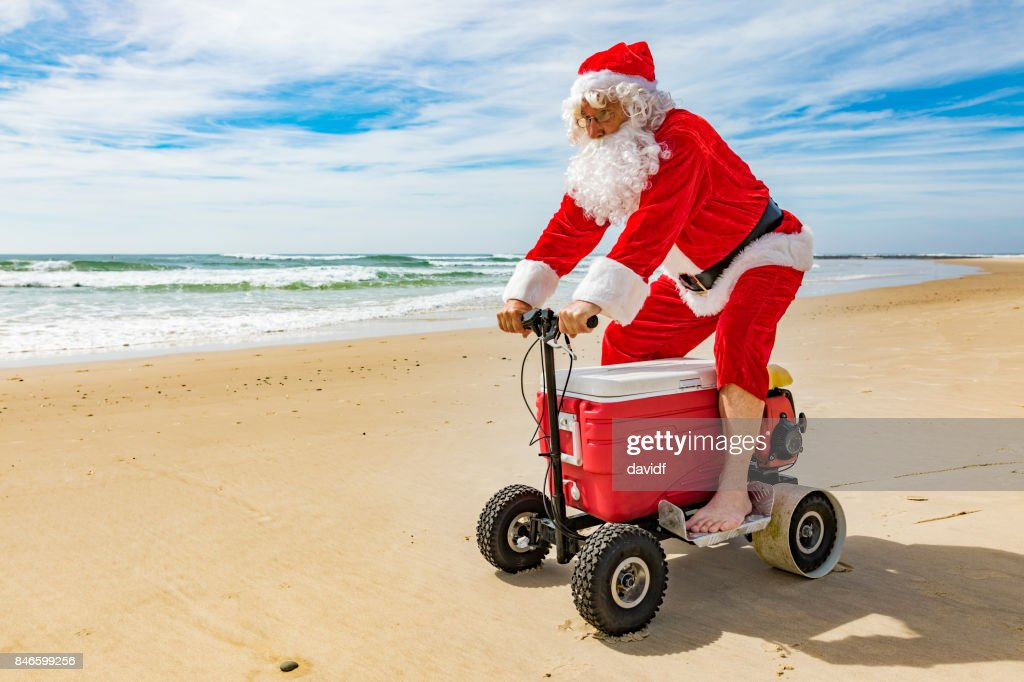 Santa Claus Riding a Motorised Esky Cooler on the Beach : Stock Photo