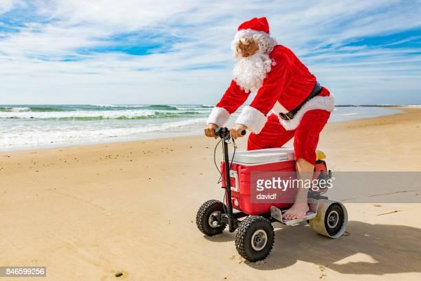 Santa Claus Riding a Motorised Esky Cooler on the Beach