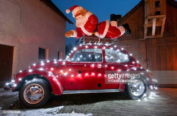 A Santa Claus sculpture is fixed on the roof rack of a Volkswagen Beetle vintage car decorated with a light chain on December 19 2018 in front of a...