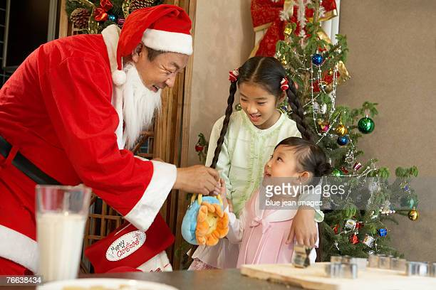 Santa Claus sending gifts to two kids.