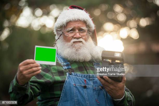 Santa Claus showing a photo taken with an instant camera