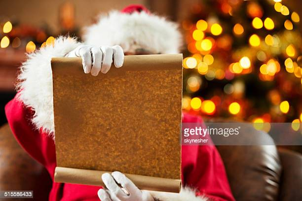 Santa Claus showing blank paper.