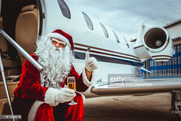 santa claus sitting just outside of a private jet parked on an airport tarmac with a glass of champagne, giving thumbs up - taxiway stock pictures, royalty-free photos & images