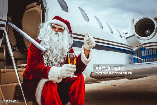 santa claus sitting on the boarding stairs of a private airplane parked on an airport runway, holding a glass of sparkling wine and giving thumbs up - taxiway stock pictures, royalty-free photos & images