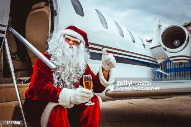 santa claus sitting on the boarding stairs of a private jet parked on an airport taxiway, holding a glass of sparkling wine and giving thumbs up while looking at the camera - taxiway stock pictures, royalty-free photos & images