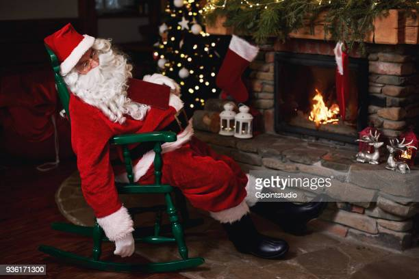 santa claus, sleeping in chair beside fireplace - santa close up stock pictures, royalty-free photos & images