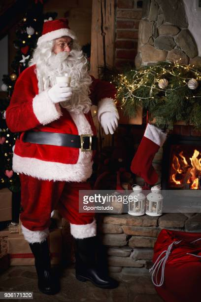 santa claus standing beside fireplace, holding glass of milk - santa close up stock pictures, royalty-free photos & images