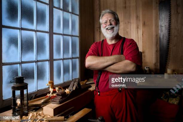 cheerful santa claus laughing in his christmas workshop, copy space - santas workshop stock photos and pictures