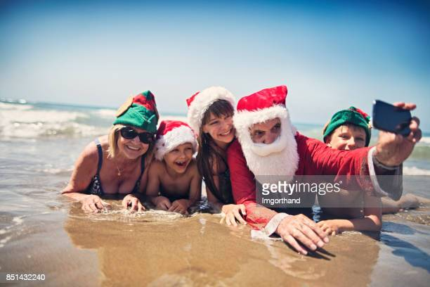 Santa claus taking selfie with family on beach