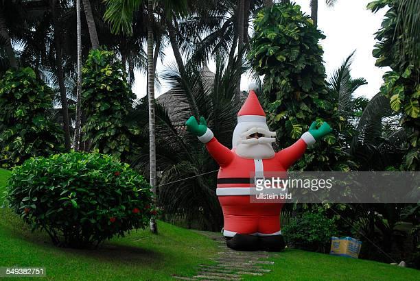 Santa Claus under palm trees Christmas decoration in the Mui Ne Restort a popular holiday village in Vietnam
