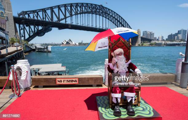 Santa Claus uses a umbrella to keep cool in the hot summer sunshine at Luna Park on December 13 2017 in Sydney Australia Luna Park has pulled some...