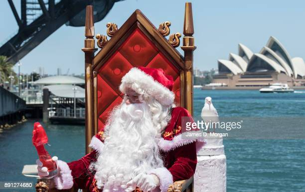 Santa Claus uses a water spray fan to keep cool in the hot summer sunshine at Luna Park on December 13 2017 in Sydney Australia Luna Park has pulled...