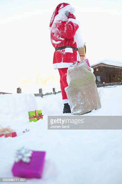 Santa Claus using mobile phone, presents in snow in foreground