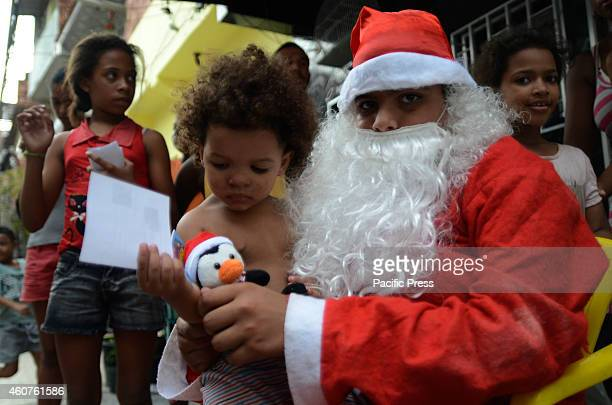 Santa Claus visits the Favela da Mare North Zone of the city and distributes gifts to children while walking through the streets