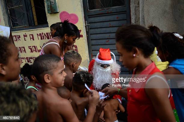 Santa Claus visits the Favela da Mare, North Zone of the city, and distributes gifts to children.