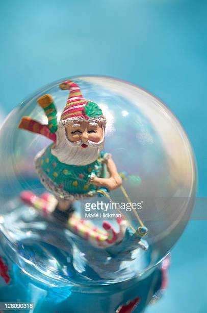 Santa Claus waterskiiing inside a snowglobe by the side of a pool