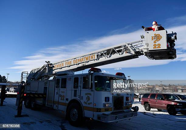 Santa Claus waves to the crowd from Denver Fire Department truck at the 86th annual Denver Santa Claus Shop at the old Kmart store near Evans Ave and...