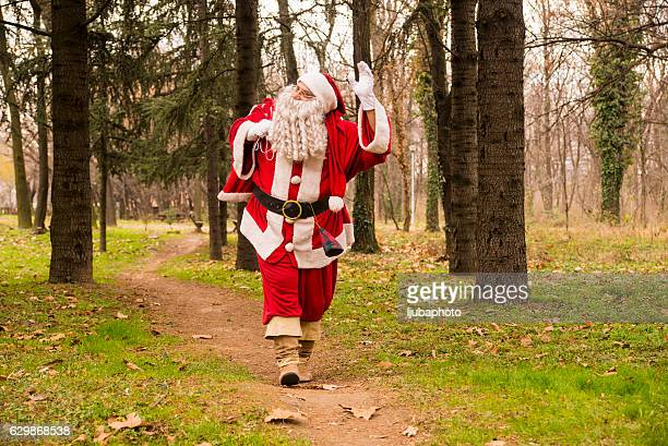 Santa Claus waving  in forest  With A bag Of Gifts