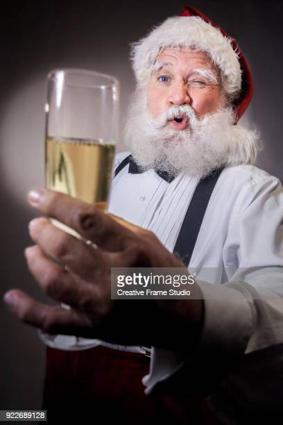 Santa Claus with a glass of champagne making a funny face