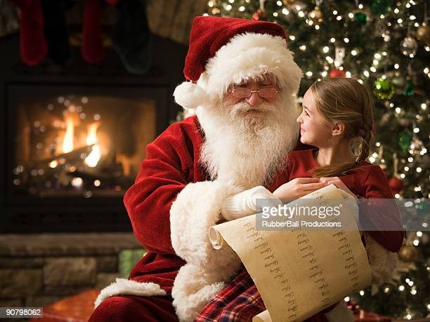 santa claus with a little girl on his lap - santa stock photos and pictures