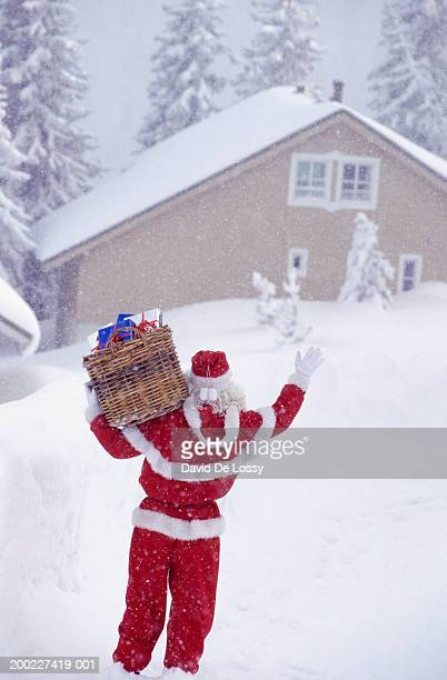 Santa Claus with basket of presents approaching house, rear view