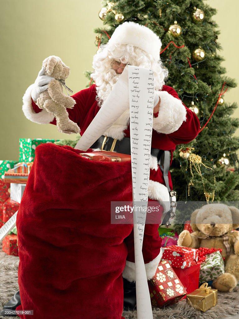 Santa Claus with checklist placing toys in bag : Foto de stock