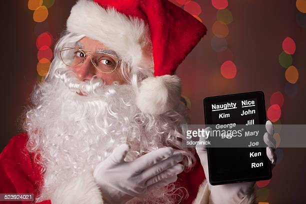 santa claus with digital naughty and nice list - naughty santa stock photos and pictures