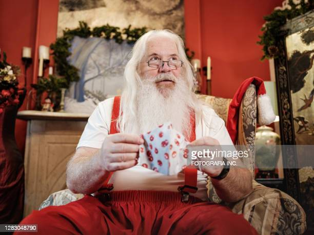 santa claus with face mask getting dressed - father christmas stock pictures, royalty-free photos & images