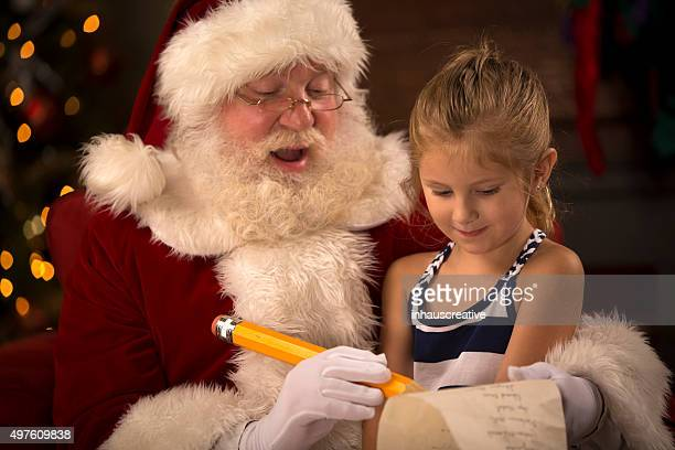 santa claus with girl going over his naughty nice list - naughty santa stock photos and pictures