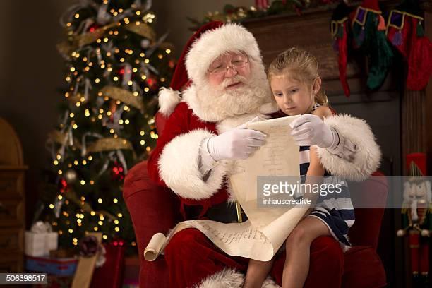 Pai Natal com Menina ler o provocadora e de nice lista