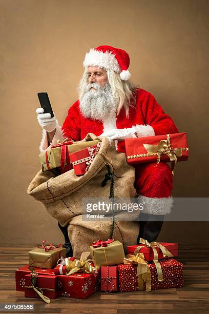 santa claus with many gifts and a phone