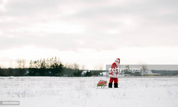 santa claus with sled and presents walking over the field - babbo natale slitta foto e immagini stock
