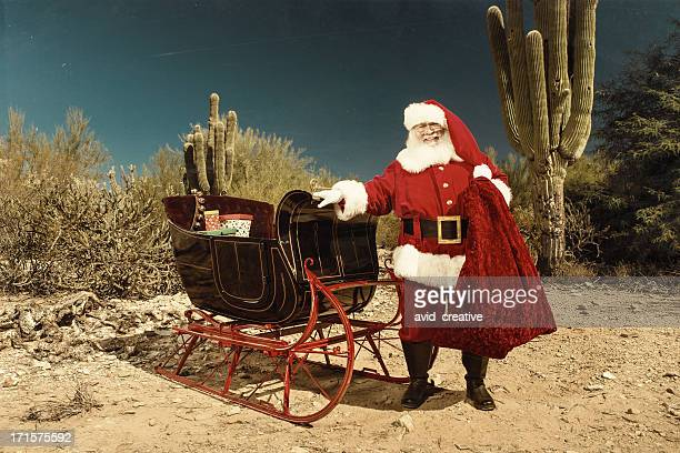 Santa Claus with sleigh in desert