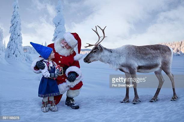 Santa Claus with young girl and reindeer