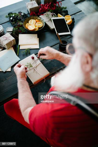 Santa Claus wrapping presents in his living room