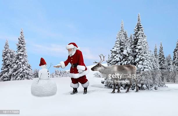 Santa Clause gives a snowman a nose