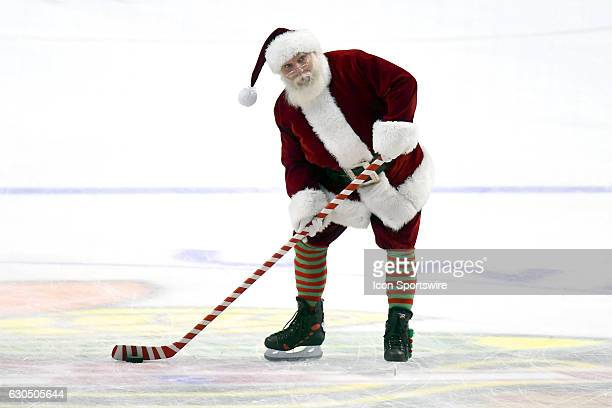 Santa Clause shoots the puck before the start of the third period of a game between the Colorado Avalanche and the Chicago Blackhawks on December 23...