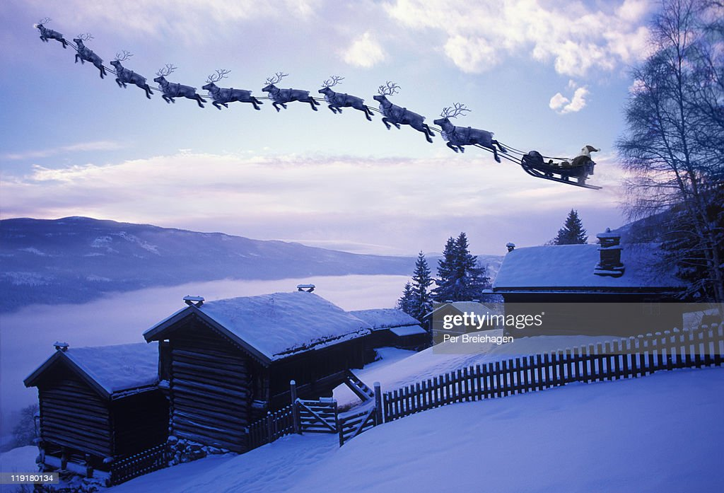 Santa Clause with reindeer flying above a farm : Stock Photo