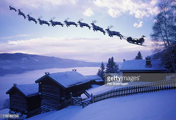 santa clause with reindeer flying above a farm - reindeer stock pictures, royalty-free photos & images