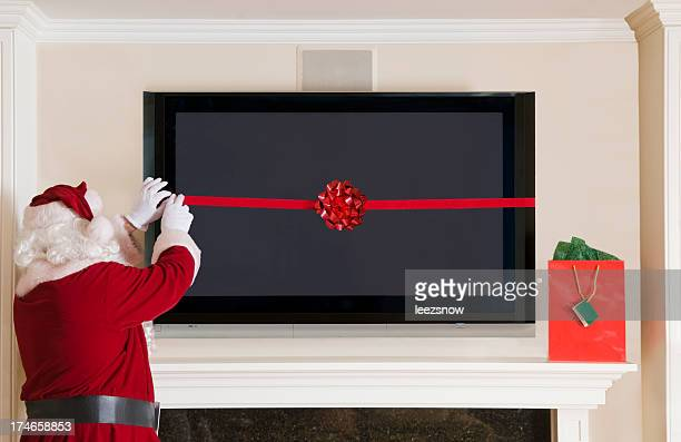Santa Clause Wrapping a Big Screen TV