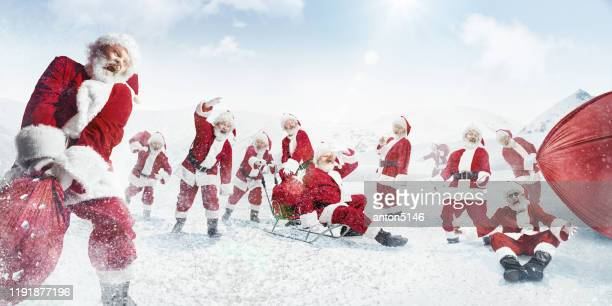 weihnachtsmänner ziehen säcke mit geschenken auf schlitten im schneebedeckten winter auf hintergrund - eisheilige stock-fotos und bilder